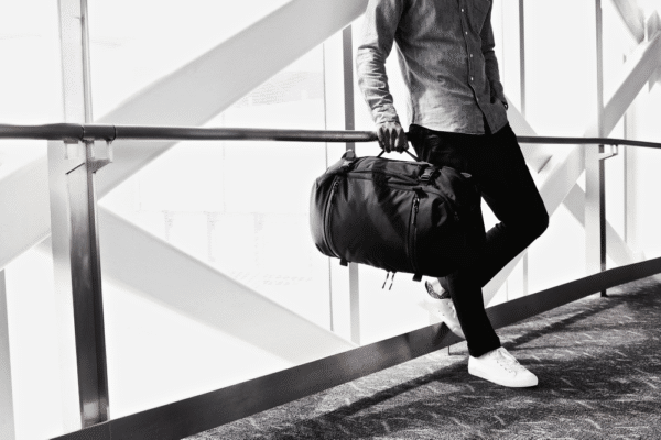 A man Posing with a traveling hand bag.