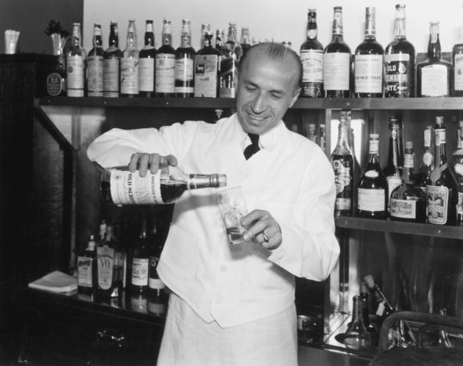 vintage bartender pouring bourbon into a glass