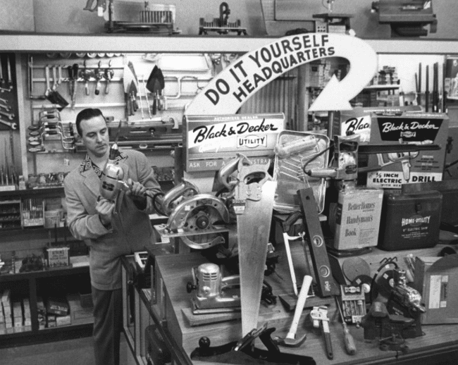 Vintage man in hardware store shopping black and decker tools.