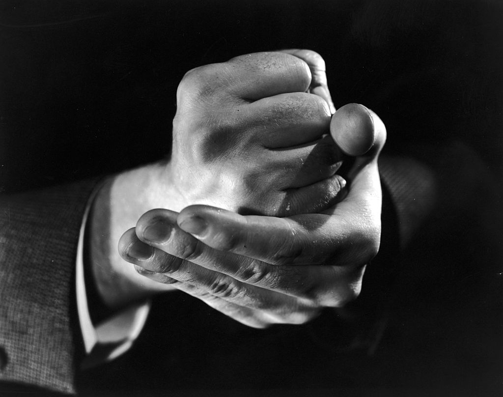 Black white photo close up of man's fist in hand.