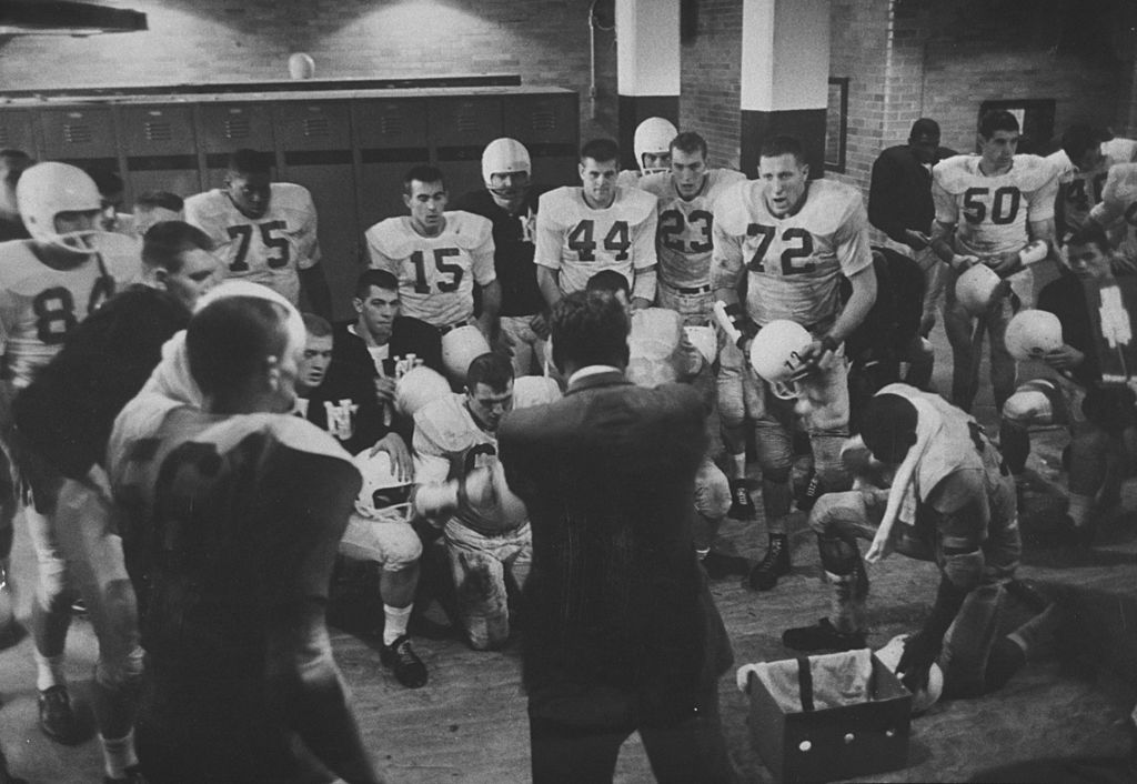 vintage locker room coach giving speech to football players