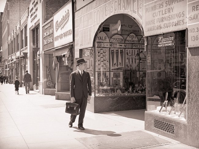 vintage businessman walking down sidewalk looking into shops