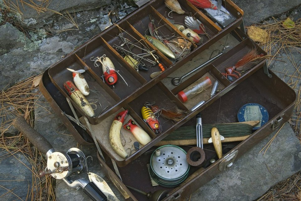 vintage tackle box with lures and fishing line