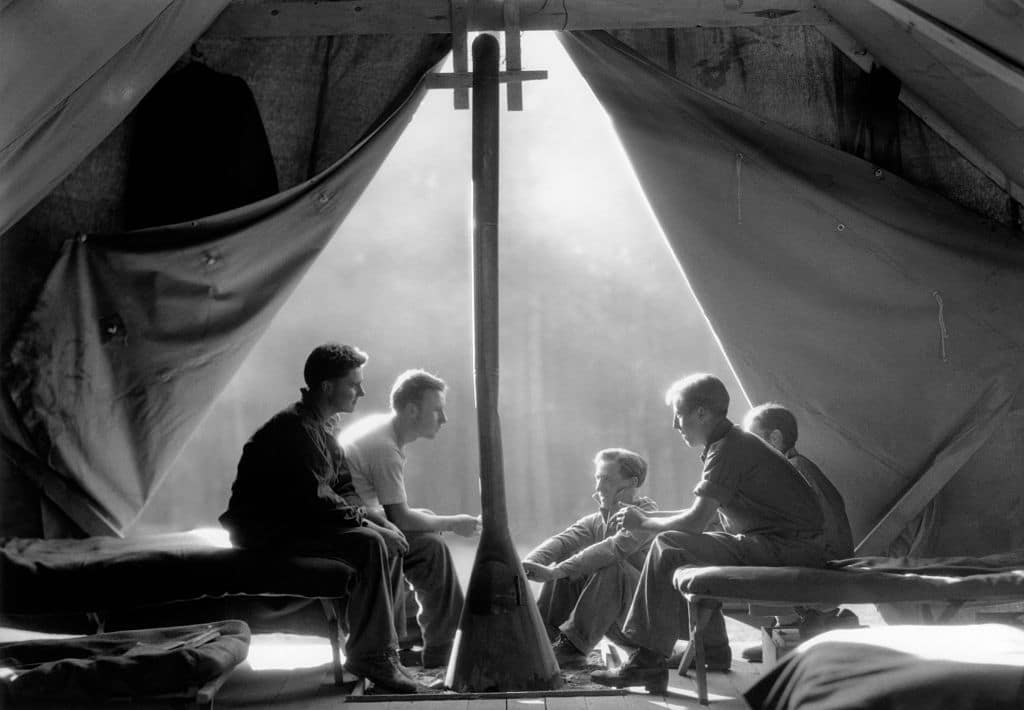 vintage soldiers sitting together in canvas army tent