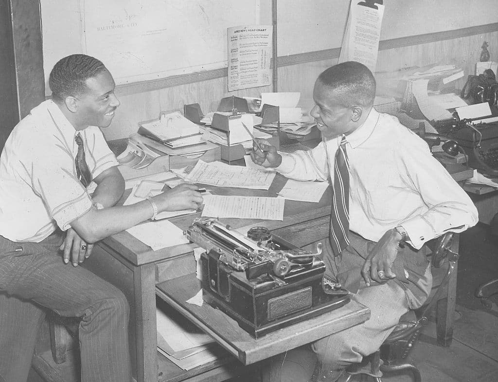 vintage men working in office at desk with typewriter