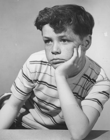 vintage boy with hand on his face pouting
