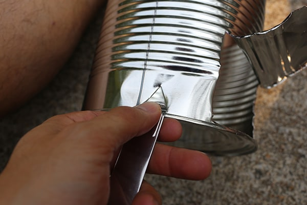 hobo stove using bottle opener to put vents in tin can