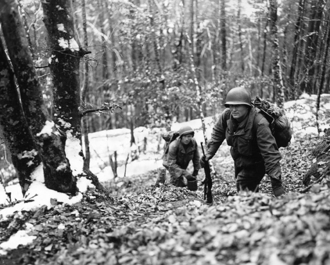 Vintage soldier walking through forest in snow and leaves.
