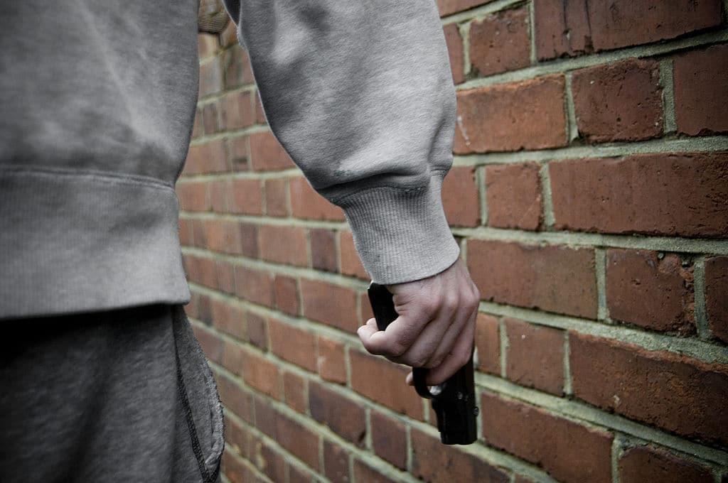Bad guy man with gun walking down street.