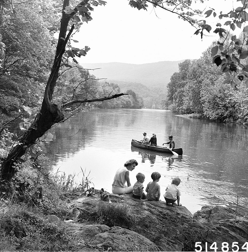 vintage family at lake canoeing sitting on rock