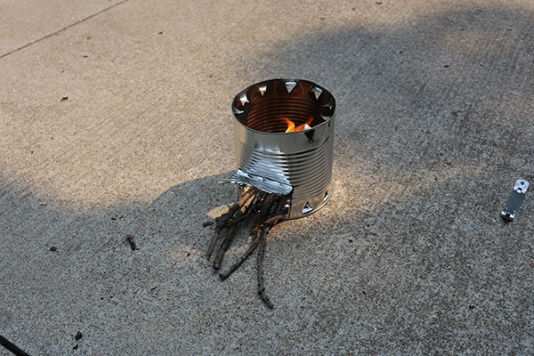 Hobo stove lit fire in a tin can.