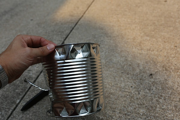 Hobo stove vents in tin can from bottle opener.