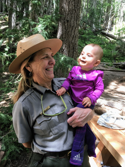 park ranger holding baby on hiking trail