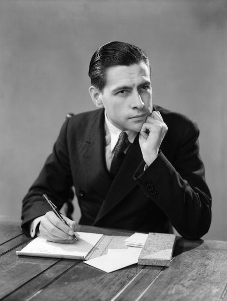 vintage man writing letter at desk pensive look