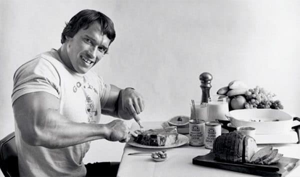 vintage arnold schwarzenegger eating steak smiling