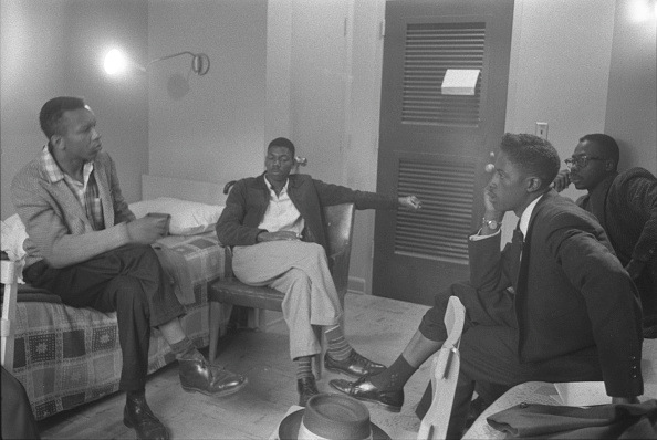 vintage young men sitting around talking in a room