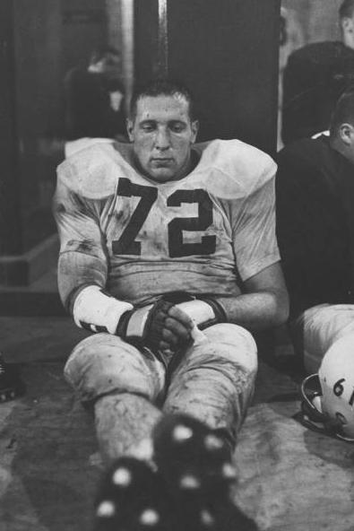 Vintage football player sulking in locker room.