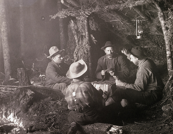 vintage men outside playing cards in the woods