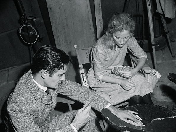 Joan Fontaine and Louis Jourdan playing cards backstage