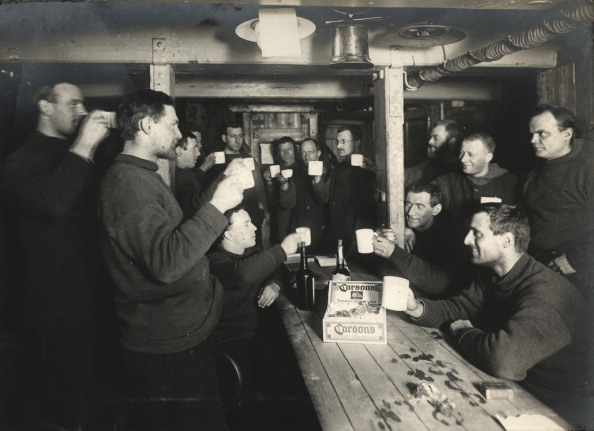 Vintage group of men giving a toast in a meeting hall.
