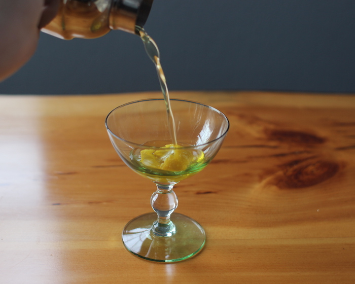 pouring vesper martini from cocktail shaker