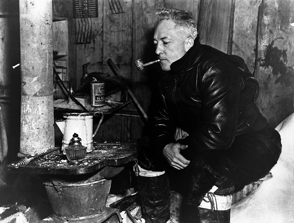 Admiral Richard Byrd smoking pipe sitting in a hut.