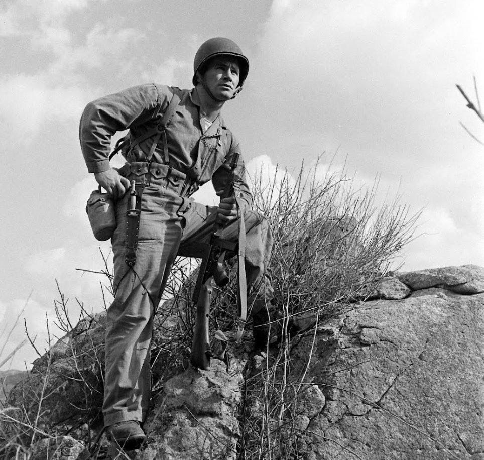 Soldier standing on mountain.