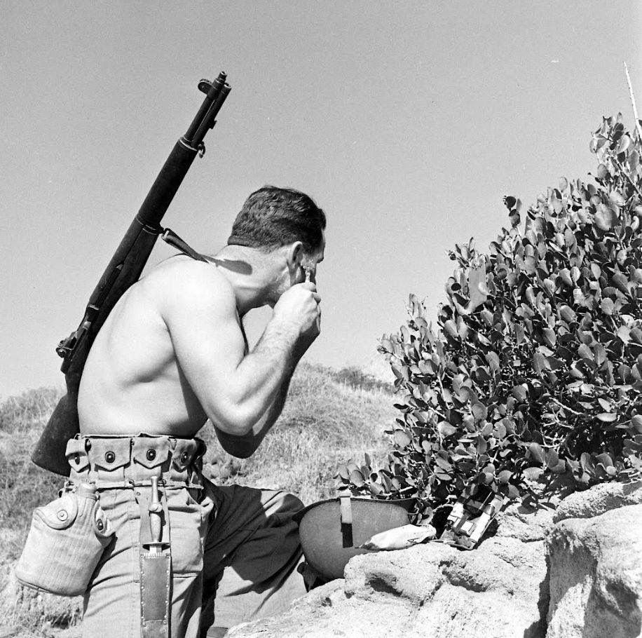 Soldier doing shaving at mountains with gun on his back.