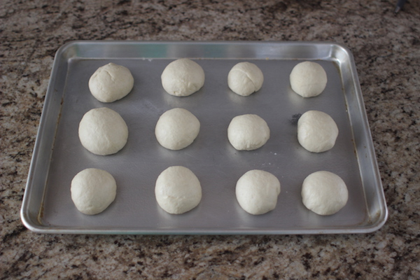 homemade english muffins dough balls on baking sheet