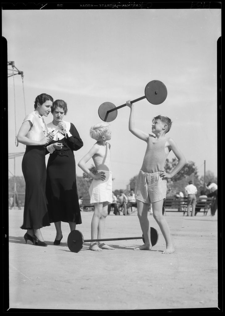 vintage young boy lifting dumbbell teachers look worried