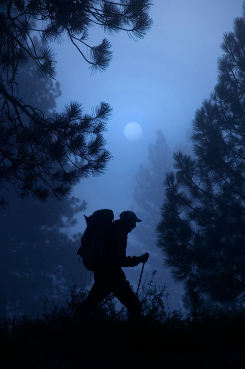 Man hiking on a mountain late at night.