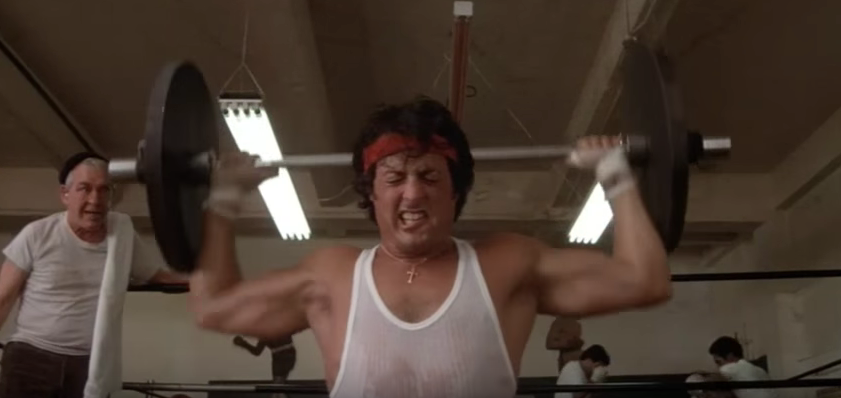 Rocky doing barbell presses while training.