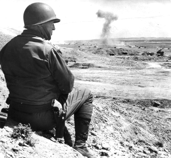 Soldier with a pistol watching out while sitting on a rock.