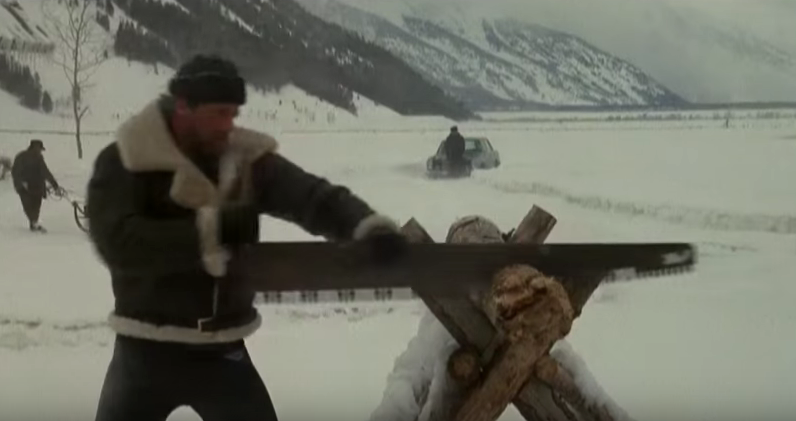 Rocky sawing wood in snow.