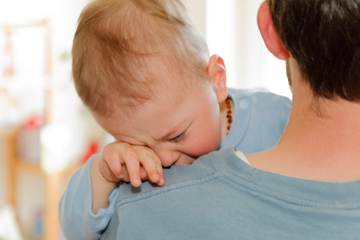 baby sick crying on dad's shoulder