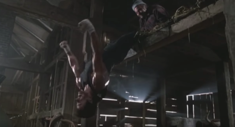 Rocky doing sit-ups with punches while hanging.