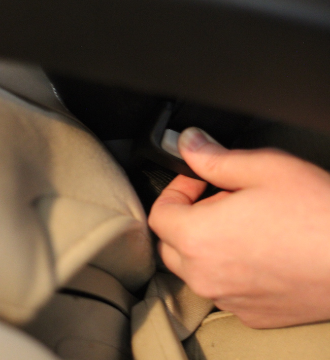 Pressing of seat belt to loosen the strap.