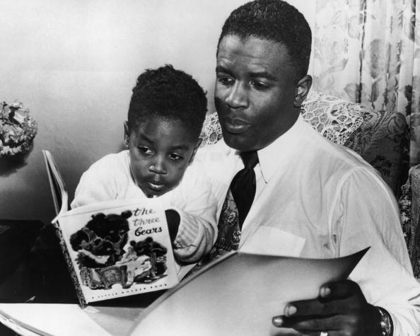 Vintage dad reading book with young son.