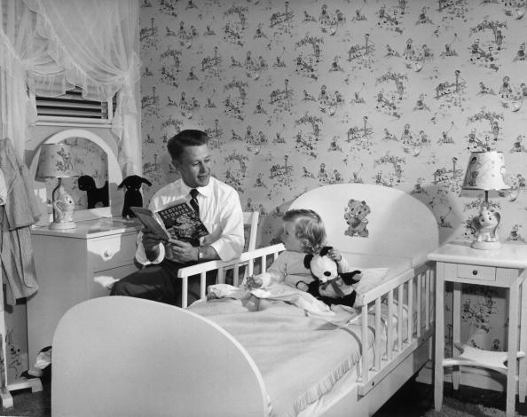 Vintage dad looking at his child while reading book.