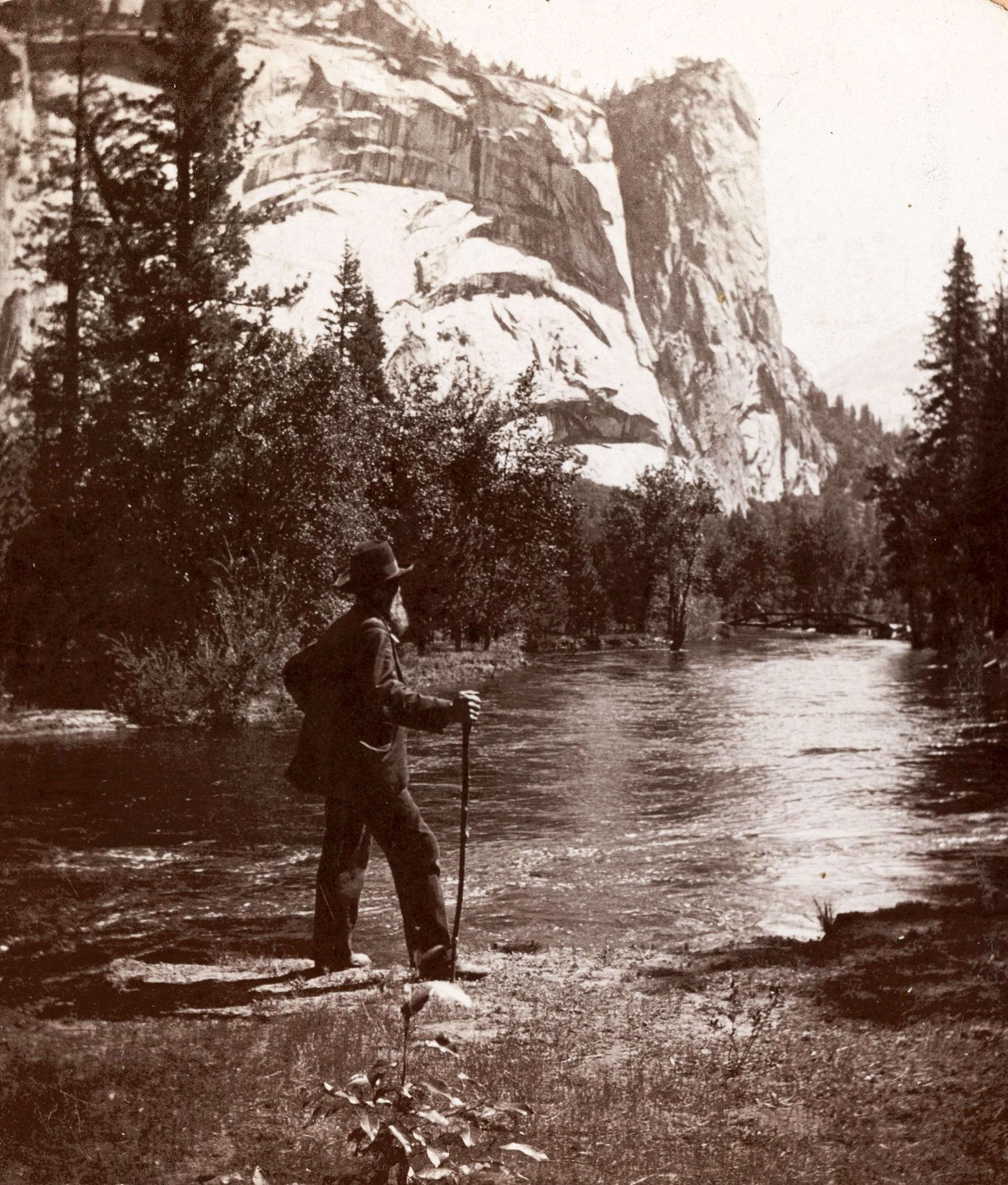 John Muir standing besides river at Yosemite valley.