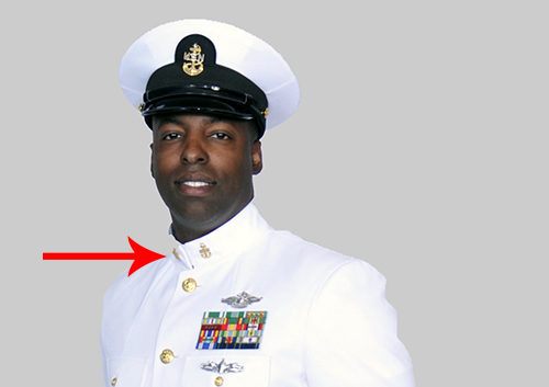 Chief petty officer in uniform has pins on both sides of the collar.