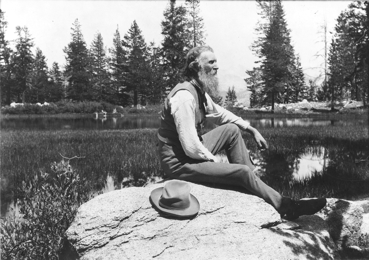 Vintage man sitting on a rock near a lake.