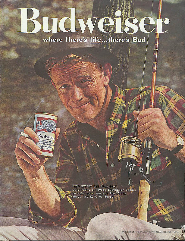 Vintage man holding Budweiser can and fishing rod in another hand.
