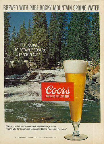 Vintage glass of Coors in glass and scenery in background.