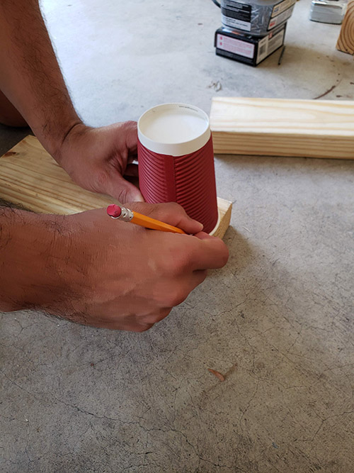 Marking a circle pattern on wood with glass.