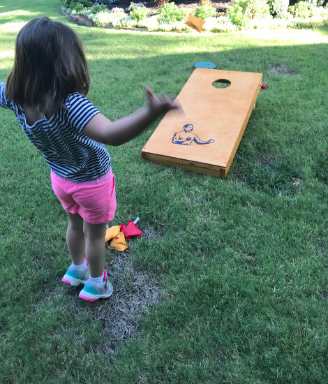 Girl standing in front of Cornhole.