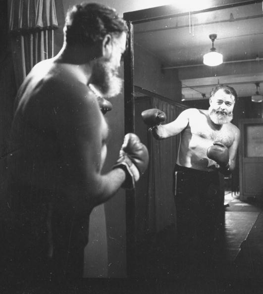 Hemingway in boxing gloves and watching him self in the mirror.
