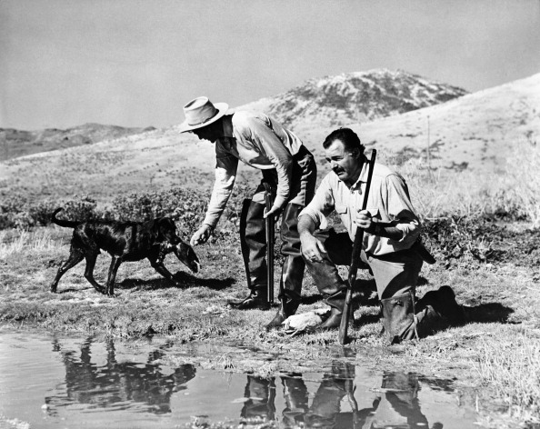 Vintage hunters with dog and carrying the guns on a river side.