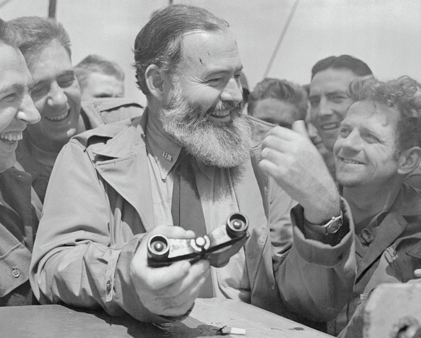 Hemingway holding Binocular and smiling with group.