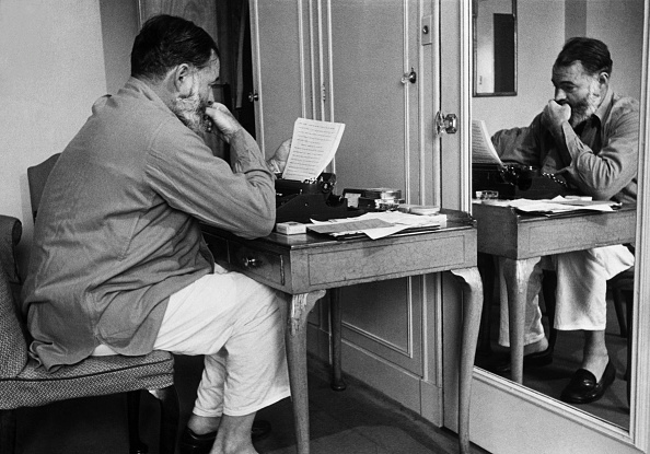 Hemingway reading notes while sitting in front of mirror.